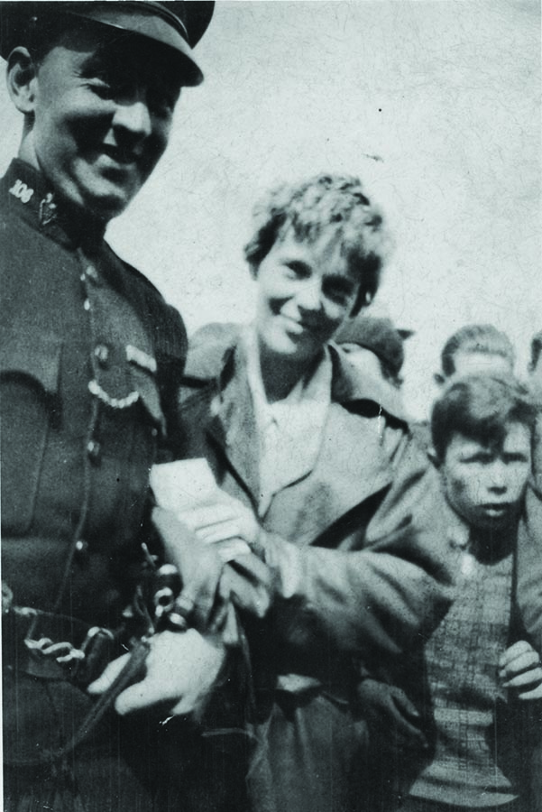 Amelia Earhart escorted by an RUC sergeant due to crowds at landing site