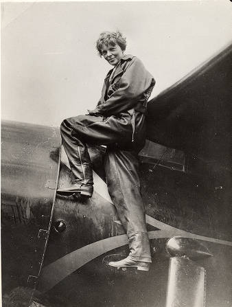 Earhart posing on her plane for the media